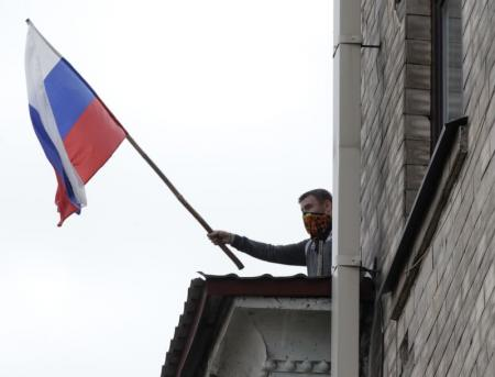 A pro-Russian activist holds a Russian flag during a storming of the regional government headquarters in Luhansk